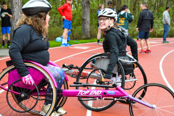 Two girls in wheelchair race chairs on track