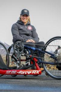 Muffy Davis in wheelchair near a hand cycle